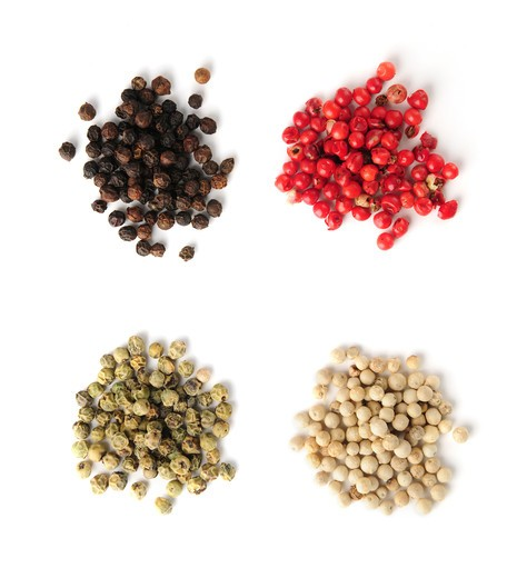 Stock Photo: 4286R-2908 Heaps of assorted peppercorns on white background, top view