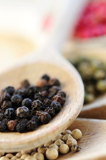 Stock Photo: 4286R-2913 Different kinds of peppercorns in wooden cooking spoons macro