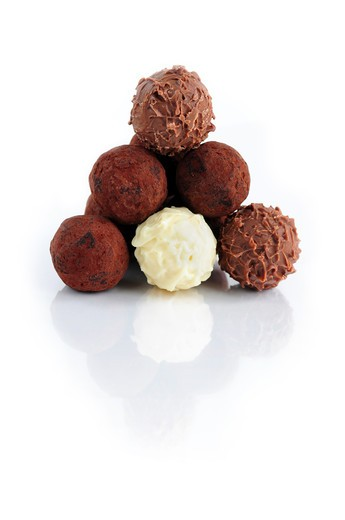 Stock Photo: 4286R-3056 Pyramid of assorted chocolate truffles on white background with reflection