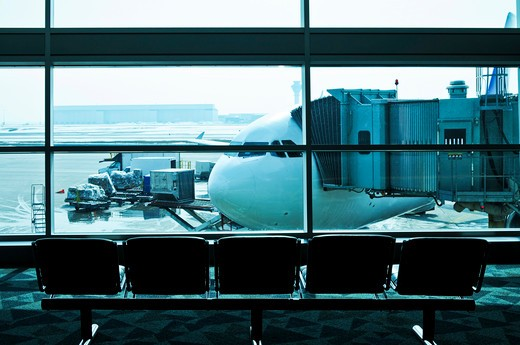 Waiting area of airport gate with airplane outside : Stock Photo
