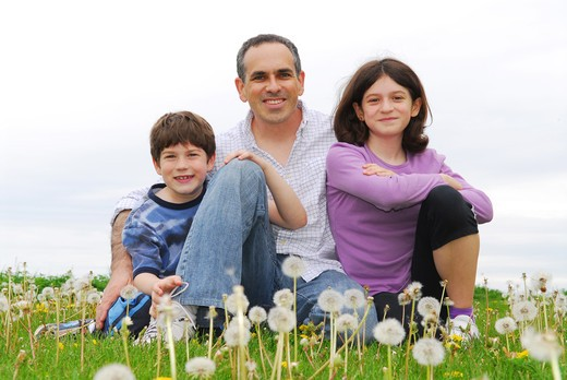 Portrait of a happy family of three on green grass : Stock Photo
