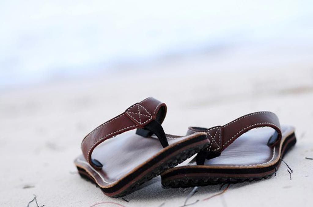 Stock Photo: 4286R-3510 Flipflops on a sandy ocean beach - summer vacation concept