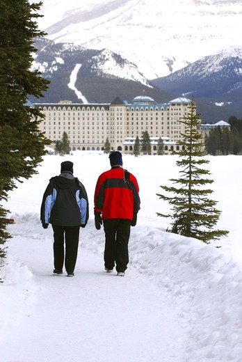 Stock Photo: 4286R-3740 A couple talking a walk in on scenic winter path at Chateau Lake Louise