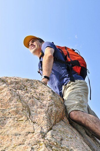 Middle aged man with backpack climbing a rock : Stock Photo