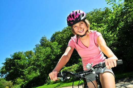 Stock Photo: 4286R-4095 Portrait of a teenage girl on a bicycle in summer park outdoors