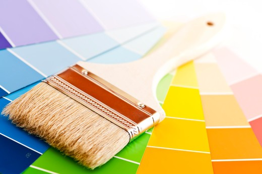 Clean paintbrush on rainbow of color card samples : Stock Photo
