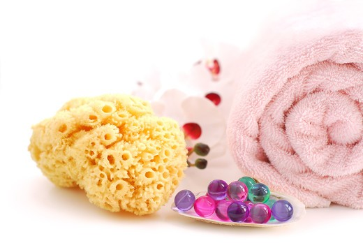 Pink rolled up towel with bath beads and natural sponge on white background : Stock Photo