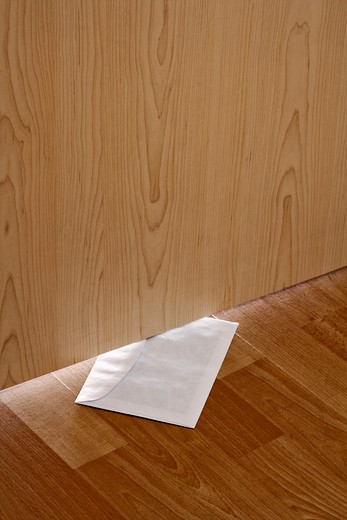 white envelope with message slipped under wooden door : Stock Photo