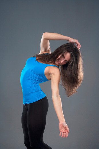 Stock Photo: 4286R-5376 energetic young woman with blue top dancing - isolated on gray background