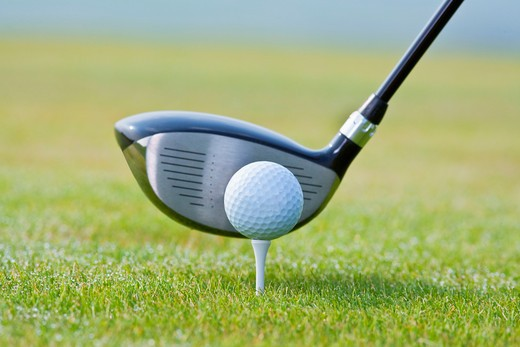 Stock Photo: 4286R-5389 closeup of a golf ball and club on green grass - club out of focus