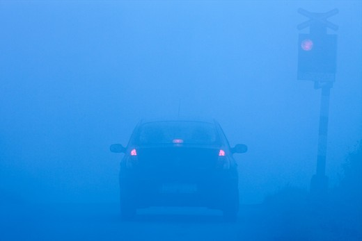 car waiting at rural railroad crossing with red lights blinking in fog : Stock Photo