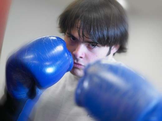 Stock Photo: 4286R-6209 Young caucasian male wearing boxing gloves looking intent