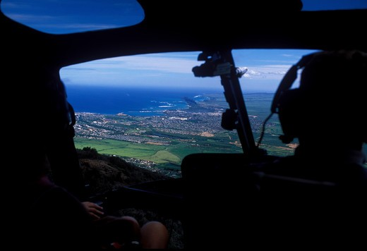 View from inside cockpit of a helicopter overlooking pinnaple fields in Maui Hawaii : Stock Photo