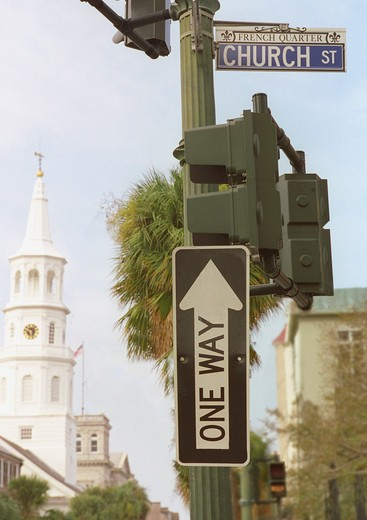 Stock Photo: 4286R-6253 A one way street sign pointing upward and  juxtaposed next to a sign for Church St. with chruch steeple in the background.