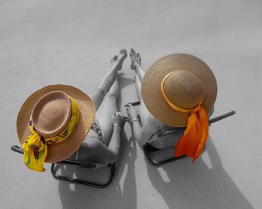Stock Photo: 4286R-6414 Birdseye view of two women sitting at pool in sun hats