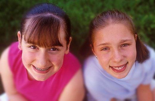 Stock Photo: 4286R-6602 Two young teenage girls with braces smiling while looking up at camera