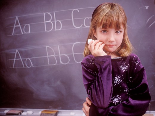 A pensive young female student holding a piece of chalk and looking at the camera. : Stock Photo