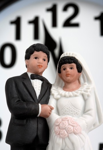Bride and groom figurines in front of midnight or noon on a clock. : Stock Photo