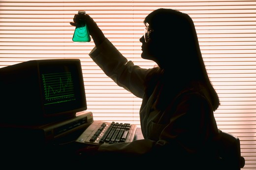Stock Photo: 4286R-9557 Silhouette of woman with beaker at computer