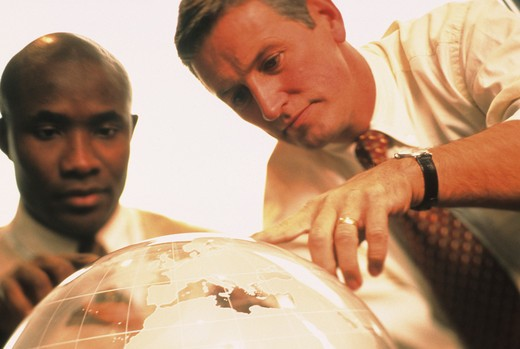 Two business men, an African-American and a Caucasian, examining a world globe. : Stock Photo