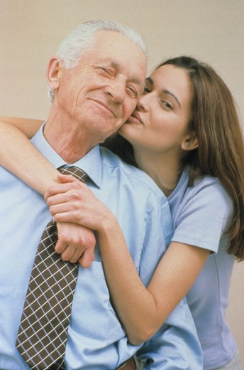 Stock Photo: 4286R-9585 MIddle aged business man with his daughter embracing him and kissing him on the cheek.
