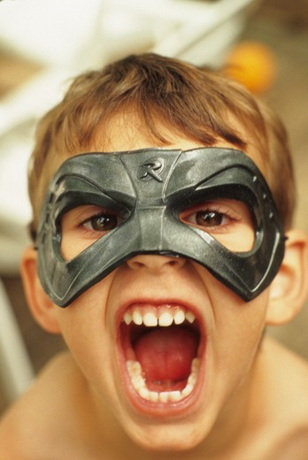 Stock Photo: 4286R-9648 Portarit of a young boy wearing a mask and shouting at the camera.