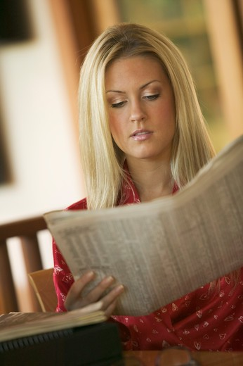 Stock Photo: 4286R-9987 Young woman reading newspaper wearing housecoat.  MR-0412  PR-0413