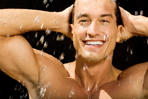 Stock Photo: 4288-1001 Muscular young man smiling at camera in shower on black background.