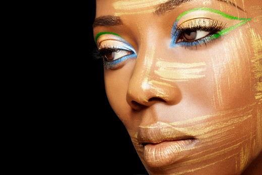 Half profile of young African-American woman painted with gold brushstrokes and bright blue and green eye shadow. : Stock Photo