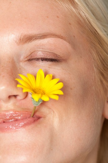 Stock Photo: 4288-1026 Blonde woman with eyes closed and yellow daisy between teeth.