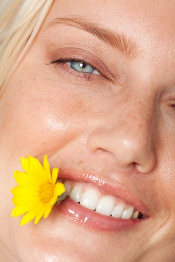 Stock Photo: 4288-1027 Blonde, blue-eyed Caucasian woman with yellow daisy between teeth.