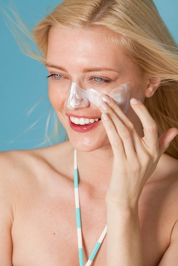 Smiling, blonde Caucasian woman applying sunscreen to her face on a blue background. : Stock Photo