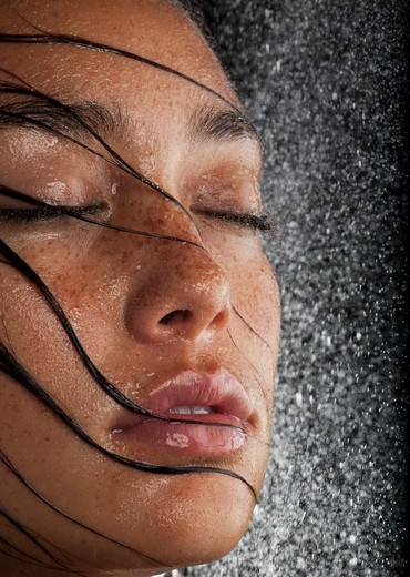 Freckled young woman with wet hair and closed eyes. : Stock Photo