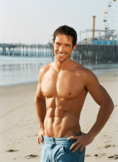 Stock Photo: 4288-1049 Muscular, shirtless man resting from run on beach.