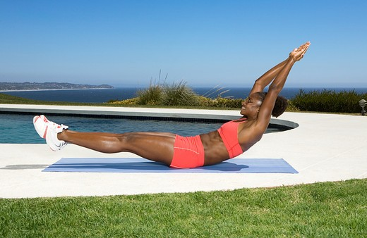 Stock Photo: 4288-1056 Young woman in orange exercising outdoors next to pool.