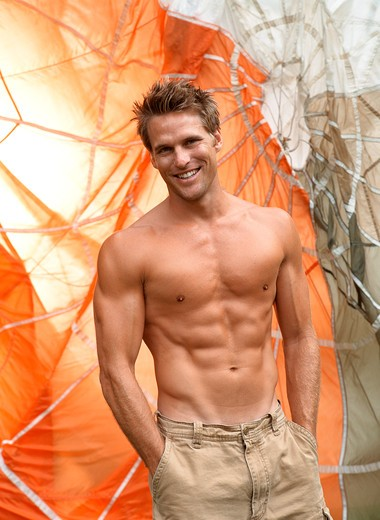 Stock Photo: 4288-1065 Shirtless Caucasian man with hands in pockets in front of parachute.