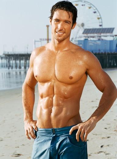 Muscular, shirtless man resting from run on beach. : Stock Photo