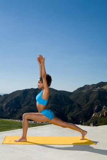 Stock Photo: 4288-1076 Young woman practicing yoga outdoors in blue shorts and sports bra.