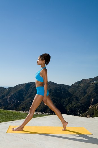 Young woman practicing yoga outdoors in blue shorts and sports bra. : Stock Photo