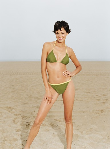 Stock Photo: 4288-1080 Young woman in green bikini on sandy beach.