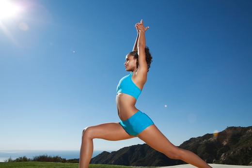 Stock Photo: 4288-1083 Young woman practicing yoga outdoors in blue shorts and sports bra.