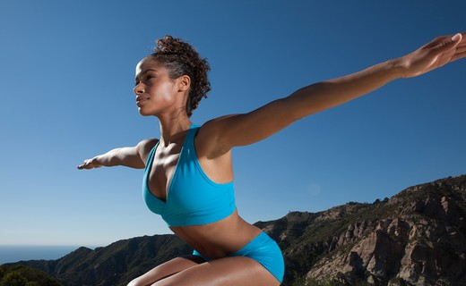Stock Photo: 4288-1087 Young woman practicing yoga outdoors in blue shorts and sports bra.