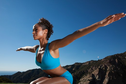 Stock Photo: 4288-1088 Young woman practicing yoga outdoors in blue shorts and sports bra.