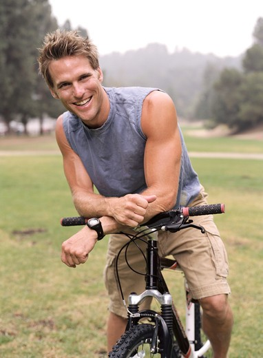 Stock Photo: 4288-1092 Muscular, young man resting on bicycle in park.