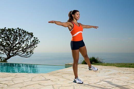 Young woman in orange and black exercising outdoors next to pool. : Stock Photo