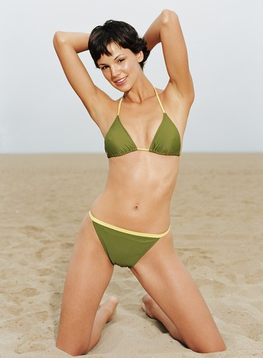 Stock Photo: 4288-1102 Young woman in green bikini on sandy beach.