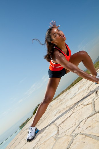 Stock Photo: 4288-1109 Young woman in orange and black exercising outdoors next to pool.