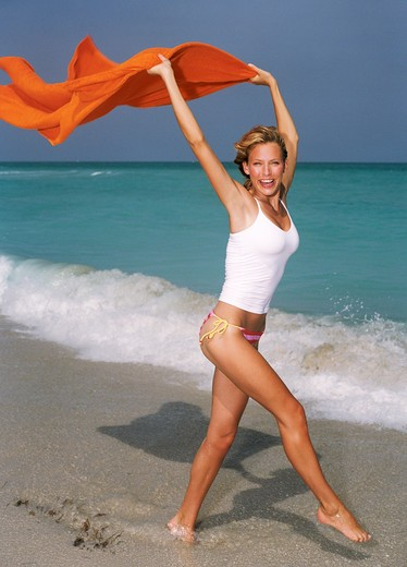 Young woman skipping on beach with orange towel. : Stock Photo