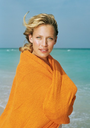 Stock Photo: 4288-1119 Young blonde wrapped in orange towel on beach.