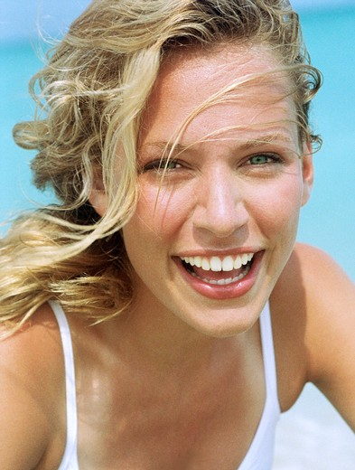Stock Photo: 4288-1120 Smiling blonde woman in white tank top.